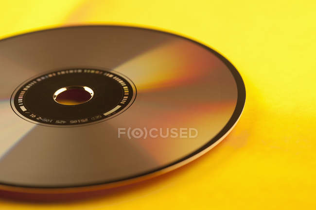 Close up view of compact disc on yellow background — Stock Photo