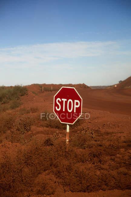 Um sinal de paragem num cruzamento num deserto — Fotografia de Stock