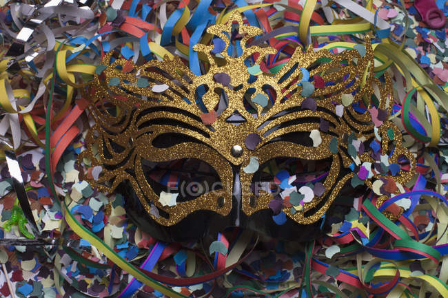 Masquerade mask nestled among confetti and streamers — Stock Photo