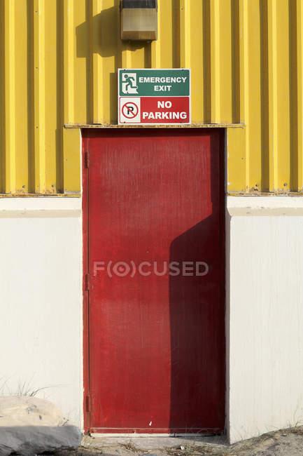 Carteles de 'salida de emergencia' y 'No Parking' en la puerta de la fachada - foto de stock