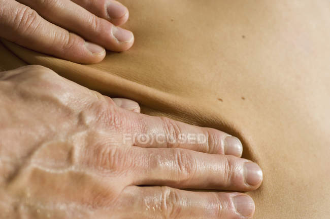 Crop male hands performing back massage — Stock Photo