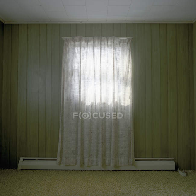 A room bare of furniture with a single curtained window — Stock Photo