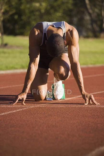 Мужчини-спортсмена в Починаючи блоки на бігова доріжка — стокове фото