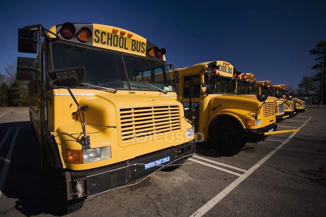 Rangée d'autobus scolaires garés en file le jour ensoleillé — Photo de stock
