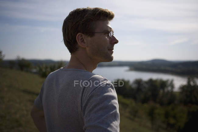 Man standing on hill and looking at view in nature — Stock Photo