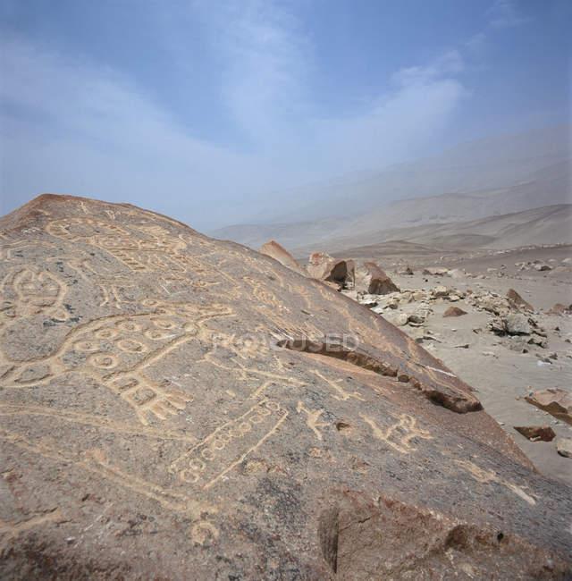 Anciennes gravures sur les rochers dans le paysage aride, Pérou — Photo de stock