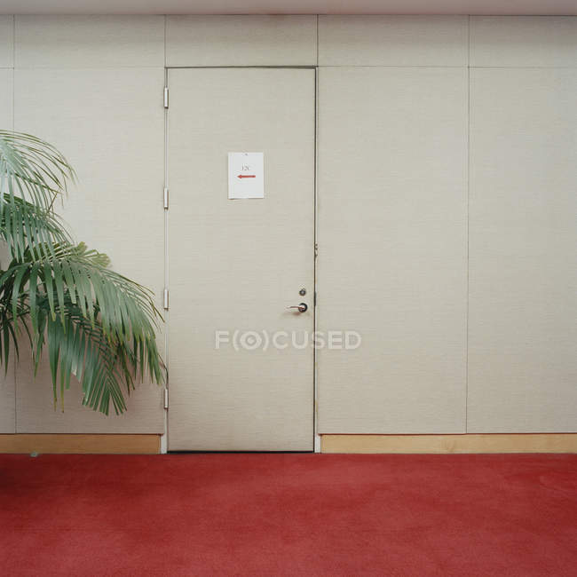 Closed door with arrow sign in beige wall at corridor — Stock Photo