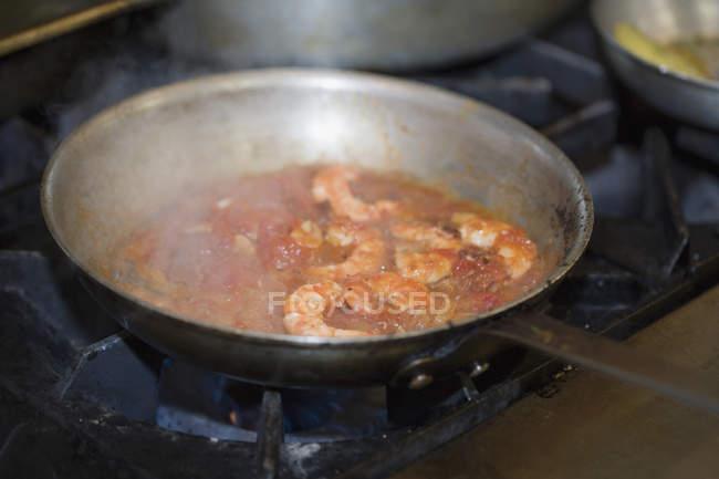 Cerrar vista de gambas y tomate salsa cocinar en una cacerola de fritada - foto de stock