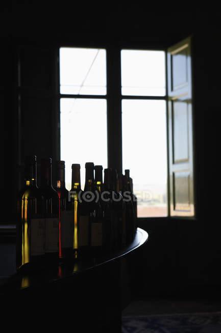 Row of various wine bottles on bar counter near open window — Stock Photo