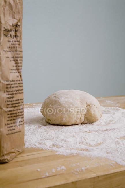 Обтинання мішок борошна і куля з тіста на кухонного столу — стокове фото