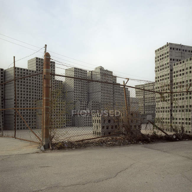 Cinder blocks stacked behind wire fence in way that resembles skyscrapers — Stock Photo