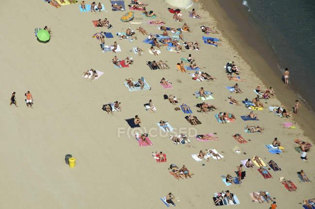 Gens reposantes sur l'eau de la plage againsy — Photo de stock