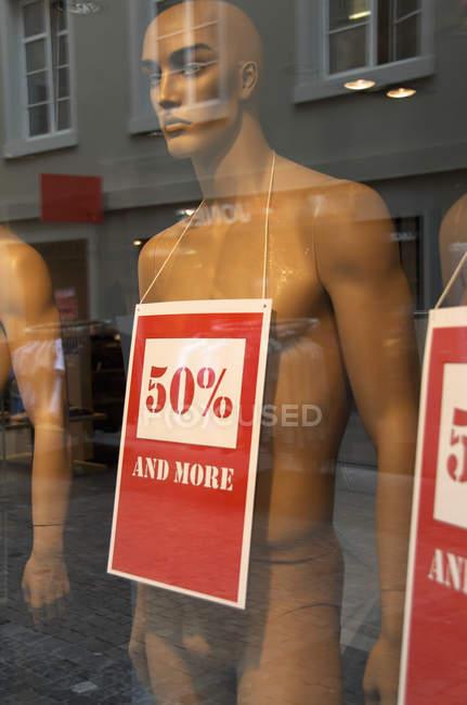 Manichino con i cartelloni pubblicitari di vendita presso negozio visualizzazione — Foto stock