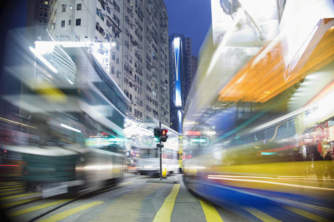 Long exposure shot of buses moving through city at night — Stock Photo
