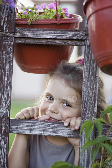 Una ragazza sorridente che osserva attraverso un traliccio — Foto stock