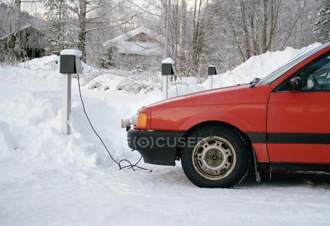 Carro vermelho de cultura ligado ao cabo elétrico no inverno ao ar livre — Fotografia de Stock