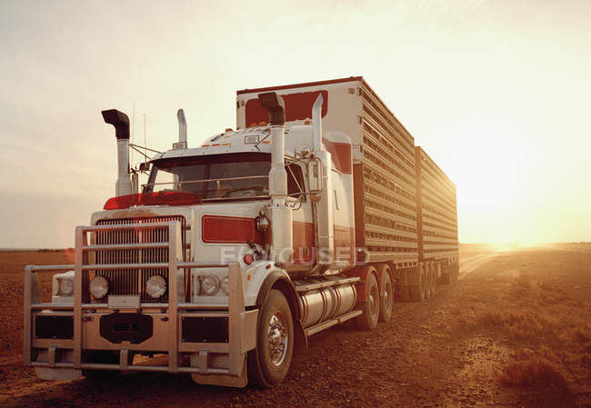 Semi-truck moving in remote landscape at sunset — Stock Photo