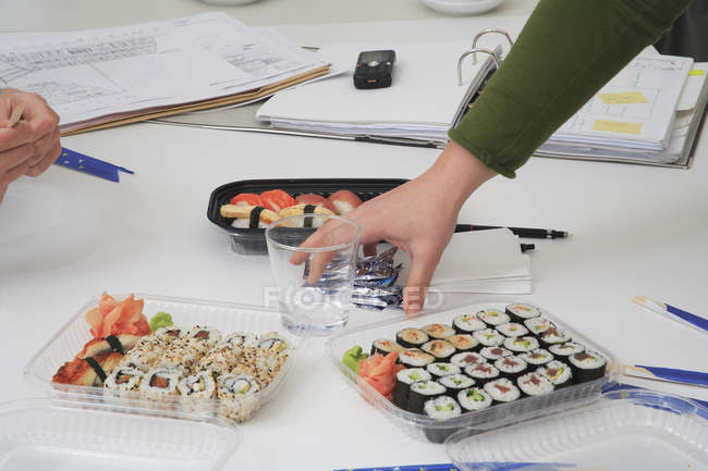 Crop hands arranging sushi lunch at workplace — Stock Photo