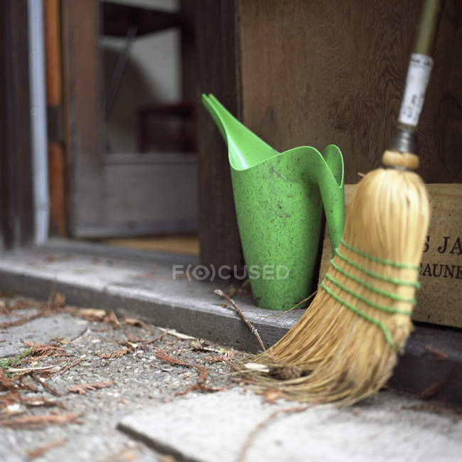 A broom and watering can outside doorway — Stock Photo