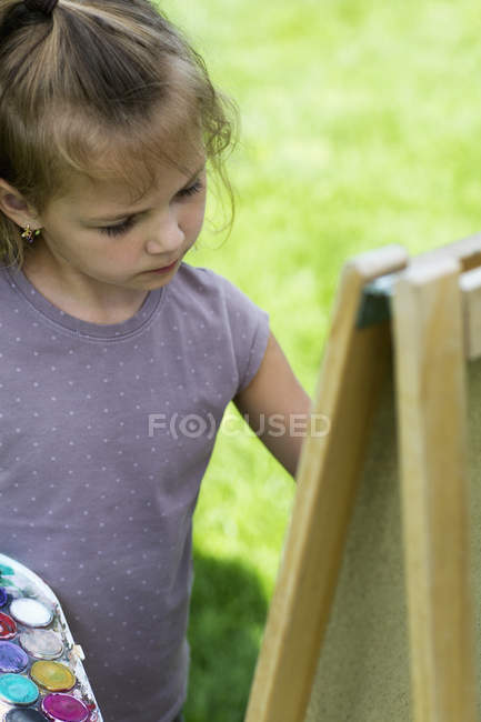 A young girl concentrating seriously while she's painting on an easel — Stock Photo