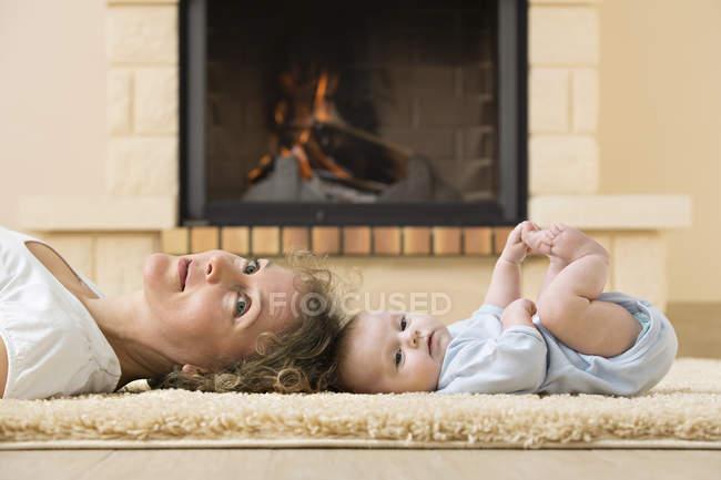Mère et fille couchées tête à tête sur le tapis devant le feu — Photo de stock