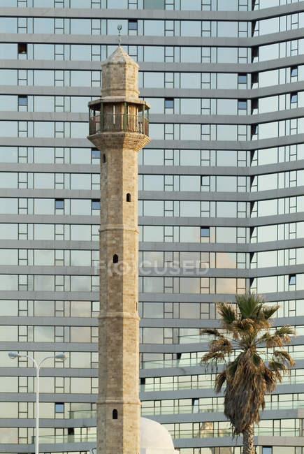 Minareto di moschea di fronte al moderno blocco di uffici — Foto stock