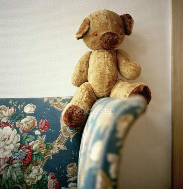 Ретро плюшевого ведмедика, сидячи на дивані квітковим малюнком — стокове фото
