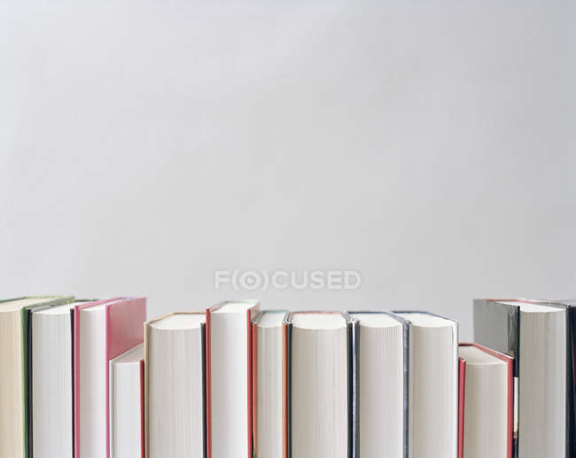 Crop row of books over grey wall — Stock Photo