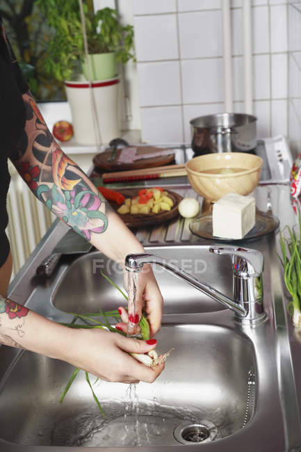 Woman washing vegetables at sink, with tattooed arm — Stockfoto