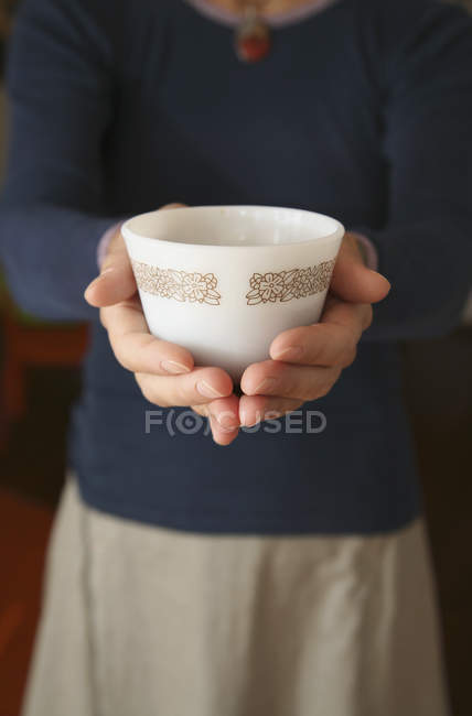 Woman holding coffee cup in palm of hands - foto de stock