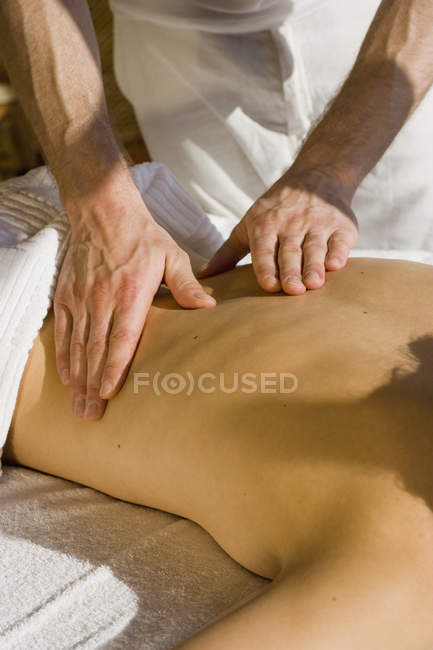 Young woman lying on front receiving back massage — Stock Photo