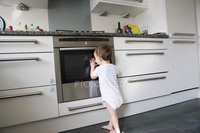 Niño apoyado en la puerta del horno y leerlo dentro de - foto de stock