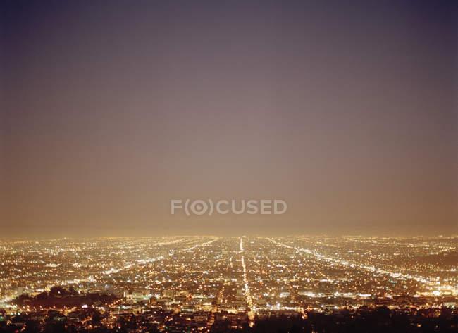 Scenic view to illuminated cityscape at night dusk — Stock Photo