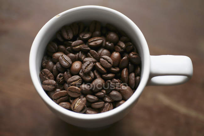 Coffee cup full of roasted coffee beans — Stock Photo