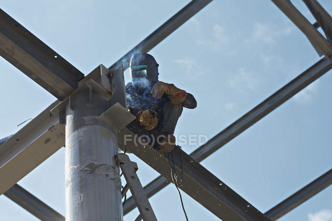 Low angle view of welder working high up on steel beam — Stock Photo