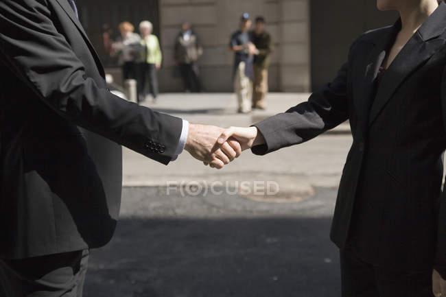 Бізнес-леді рукостисканням зі бізнесмен міста, на вулиці — стокове фото