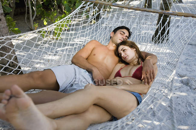 Relaxed young couple lying down on hammock — Stock Photo