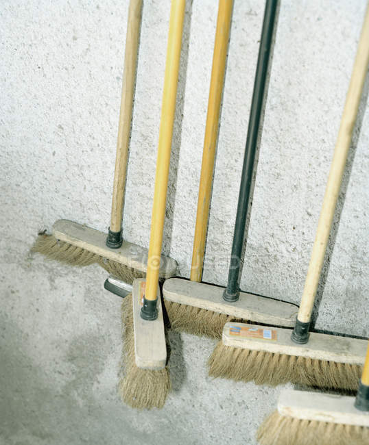 Crop collection of brooms leaning on wall — Stock Photo