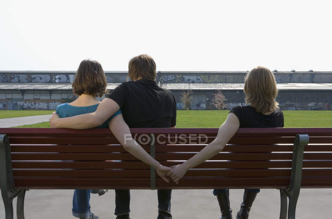 Rear view of man hugging girl holding hands behind park bench — Stock Photo