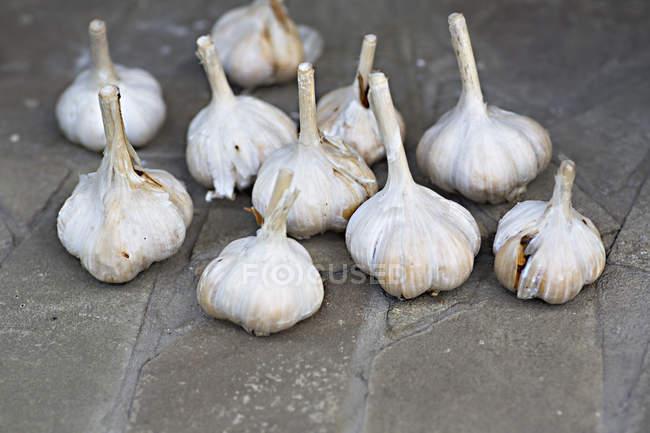Куча луковицы чеснока на каменных детектированных — стоковое фото