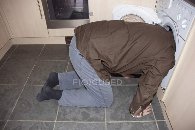 Man kneeling down with head in washing machine — Stock Photo