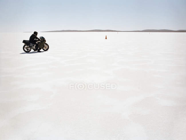Side view of man on motorcycle at sunlit salt flat — Stock Photo