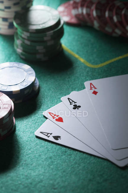 Hand of cards displaying four aces by gambling chips in background — Stock Photo