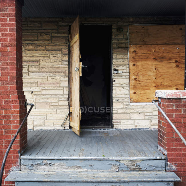 Detail an open door of a boarded up house — Stock Photo