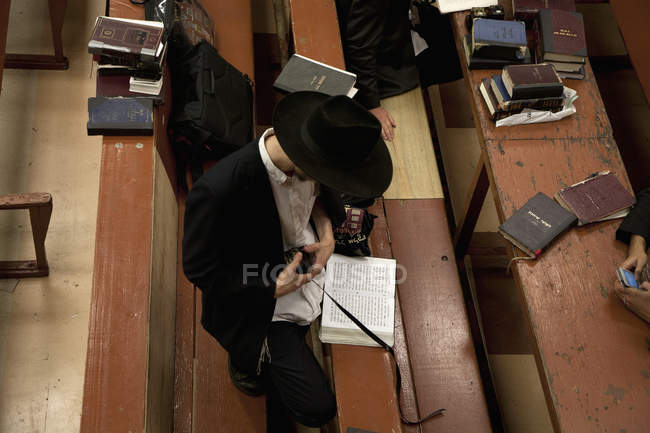From above view of jewish man holding tefillin in synagogue — Stock Photo