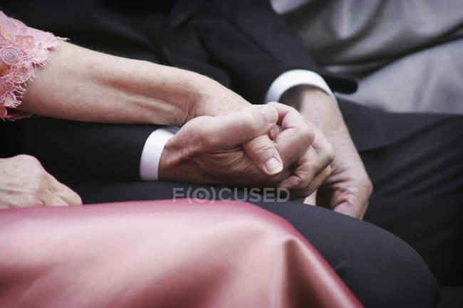 Кадроване зображення чоловік і жінка в формального одягу, тримаючись за руки — стокове фото