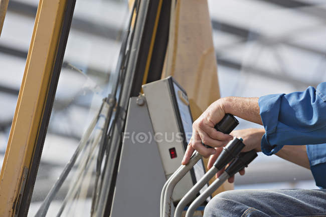 Cropped image of backhoe driver's hand on steering levers — Stock Photo
