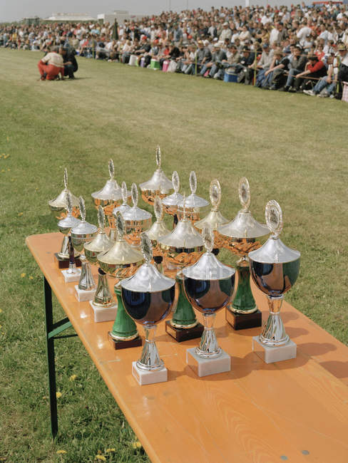 Trophies on table at sports event with spectators on background — Stock Photo