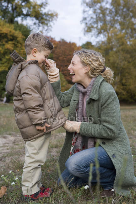 Mother pinching son nose in park whilst zipper up parka — Stock Photo