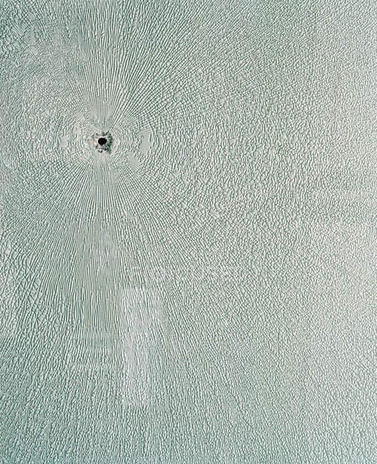 Повний слави постріл дірка від кулі в текстурованою поверхні — стокове фото